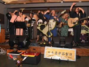 畳と一体化した楽器を演奏しながら畳の魅力を歌ったバンド「日本畳楽器製造」=22日、奄美市笠利町の「koya cafe」