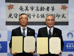 高齢者等見守りに関する協定書を交わした(右から)朝山市長と松薗理事長=18日、奄美市役所
