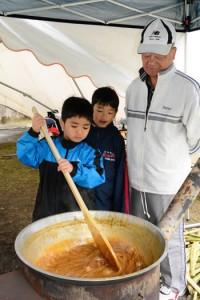 地域住民に教わりながら黒糖を作る児童=1月30日、大和村の大和小学校