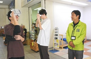 VR機器で徳之島の秘境や観光地の映像を楽しむ観光客=22日、徳之島町亀徳新港