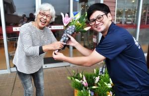 花束を笑顔で受け取る女性=14日、知名町