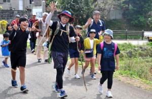 青空の下、えらぶ路を元気に歩く大城小の6年生や保護者、教諭ら=29日、和泊町谷山