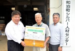 前田さん(左)に寄付箱を贈る平山理事長