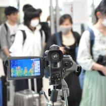 奄美空港到着ロビーに設置されたサーモグラフィーと到着客=23日、奄美市笠利町