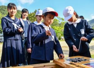 看板を設置する児童生徒たち=16日、瀬戸内町の篠川小中学校