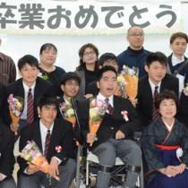 卒業式後、クラスメートや保護者らと記念写真を楽しむ鈴倉さん(前列中央)=2日、奄美市笠利町