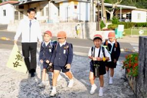 学校が再開され、元気よく登校する和泊小の児童ら=16日、和泊町