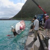 転覆した漁船の引き揚げ作業=29日午前9時10分ごろ、龍郷町安木屋場漁港(町役場提供)