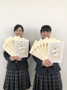 全商検定6種目1級と日商簿記検定2級を取得した樟南第二高校2年の西元さん、納沢さん(提供写真、左から)