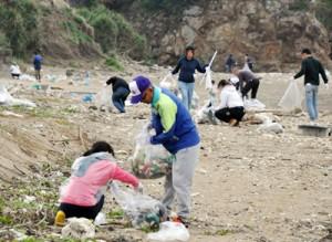 海岸のごみを拾う参加者=4日、奄美市笠利町佐仁の楠野海岸