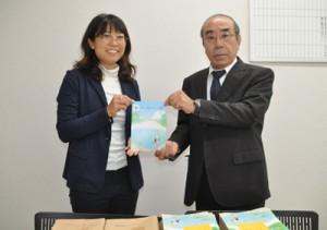 与論町の各学校の児童生徒のため冊子を寄贈した、海の再生ネットワークよろんの池田事務局長(左)=18日、同町
