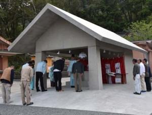 係者らが手水舎の完成を祝った竣工祭と自動給水式を採用した水栓=3日、奄美市名瀬の高千穂神社
