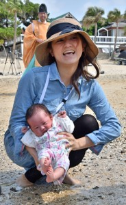 健やかな成長を願い、娘のさくらちゃんの足を海水に浸す母親のみなみさん=26日、奄美市笠利町