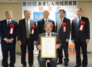 あましん地域貢献賞を受賞した徳之島虹の会の政理事長(前列)=3日、奄美市名瀬