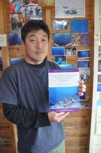 鹿児島大学総合研究博物館と共同出版した「沖永良部島の魚類目録」を手にする上原さん=2日、和泊町