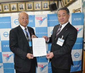 食品の無償提供で合意したフードバンク奄美の里理事長(左)と伊集院村長