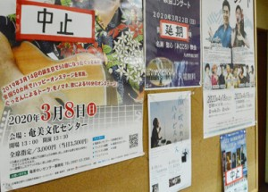 中止の張り紙が目立ち始めたアーマイナープロジェクトの掲示板=5日、奄美市名瀬金久町