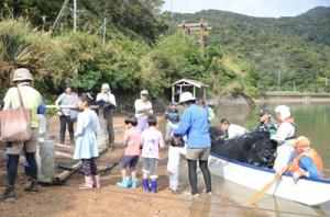 網を仕掛けるのを手伝う参加者。写真奥が見張り台=1日、宇検村芦検