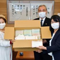 絹地でできた手作りマスクを寄贈したアーダンの西会長(左)=30日、奄美市役所