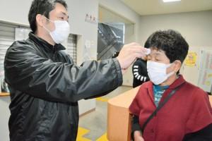 検温を受ける乗船客(右)=4日、和泊港