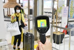 徳之島空港で運用が始まったサーモグラフィーと到着客=17日、天城町浅間