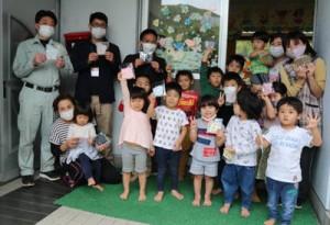 島外から贈られた手作りマスクを手に笑顔を見せる名音青壮年団の団員と大和保育所園児ら(提供写真)=20日、同村
