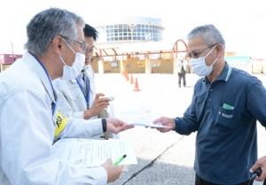 来島者へ活動自粛を呼び掛けるチラシを配る知名町職員(手前左)=15日、和泊港