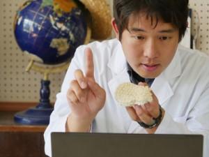 オンライン授業を行うサンゴ研の駒越太郎研究員(手にしているのはアザミサンゴの標本)=3月、喜界町