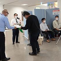 県のサーモグラフィーの隣で乗客にチラシを配布する奄美市職員ら=20日、同市笠利町