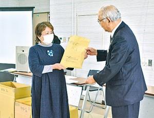 竹田泰典町長(右)から手作りマスクを受け取る隈元区長=27日、龍郷町役場