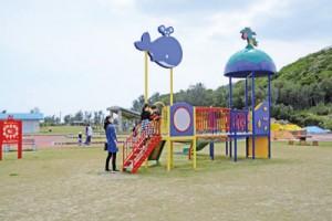 マスク姿で遊ぶ家族=25日、奄美市笠利町のあやまる岬観光公園