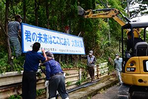 大島北高校を応援する目的で看板を設置する同校OBら=19日、龍郷町中勝