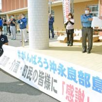 和泊町区長会の代表者に配布用のマスクを手渡す伊地知町長(右)=14日、同町役場駐車場