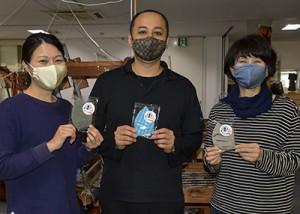 大島紬のマスク販売を開始した夢おりの郷の南代表(中央)=15日、龍郷町大勝