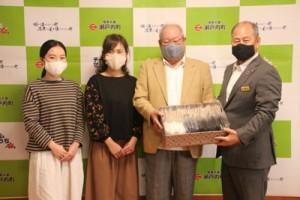 鎌田瀬戸内町長(右)に手作りマスクを寄贈する同町大島紬協同組合の元山代表理事=22日、町役場
