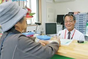 地域の高齢者に笑顔で対応する村田局長