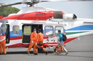 県の防災ヘリに沖永良部島内の濃厚接触者の検体を運び込む保健所職員(右)=2日午後1時20分ごろ、和泊町の沖永良部空港