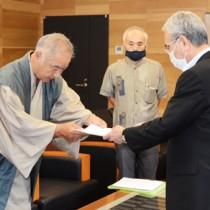 朝山市長に要望書を手渡す前田理事長(左)=18日、奄美市名瀬