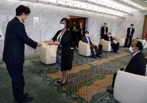 三反園知事(左)に医療用資材の目録を手渡す山田さん=21日、鹿児島市の県庁