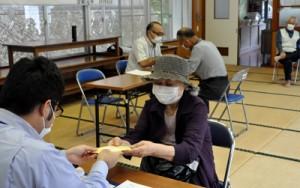 特別定額給付金の10万円を受け取る村民(中央)=8日、大和村思勝
