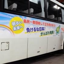 新型コロナウイルスに立ち向かう人たちへの応援メッセージを掲載したしまバスを紹介する勝村社長代理=27日、奄美市