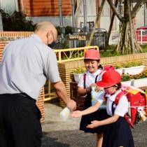 消毒液を持った道添校長に迎えられる児童=7日、奄美市笠利町の笠利小学校