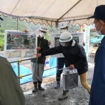 大美川の川底掘削、護岸等工事の概要などを説明する県大島支庁職員=22日、龍郷町