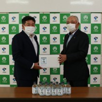 自社製の高濃度エタノール製品を寄贈した渡慶彦代表(右)と元山公知宇検村長=7日、宇検村役場