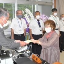伊集院村長(左)から支援金を受け取る、村内の事業者=18日、同村役場仮庁舎