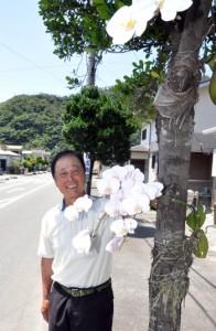 優雅な白い花を咲かせているコチョウランと重田会長=28日、奄美市名瀬大熊町