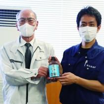 川島町長(左)に自社製の高濃度エタノールを手渡す喜禎代表=25日、喜界町役場