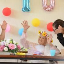 108歳の誕生日を迎えた沖永良部島最高齢の大里アキさん(中央)ら=25日、和泊町国頭