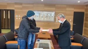 朝山市長(右)に要望書を手渡すダイビング事業者の代表ら(提供写真)=1日、奄美市役所