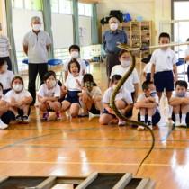 ハブを観察する児童ら=25日、奄美市笠利町